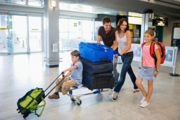 Family in airport with bags and trolley